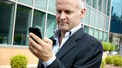 stock-footage-portrait-of-happy-businessman-with-mobile-telephone-smart-phone-typing-and-browsing-the-internet