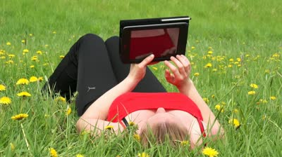 stock-footage-woman-reading-a-book-with-a-tablet-pc-in-nature-tablet-pc-and-nature