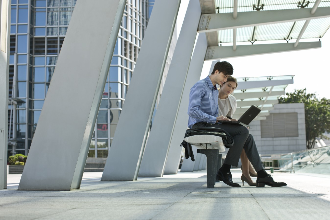 AffPro Man and Woman Sitting on Bench Using Inspiron 15R
