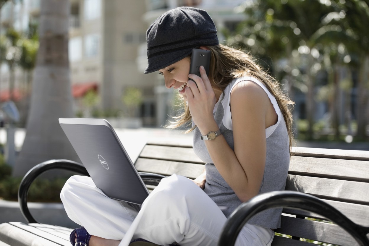 Young woman, talking on a mobile phone and using a laptop
