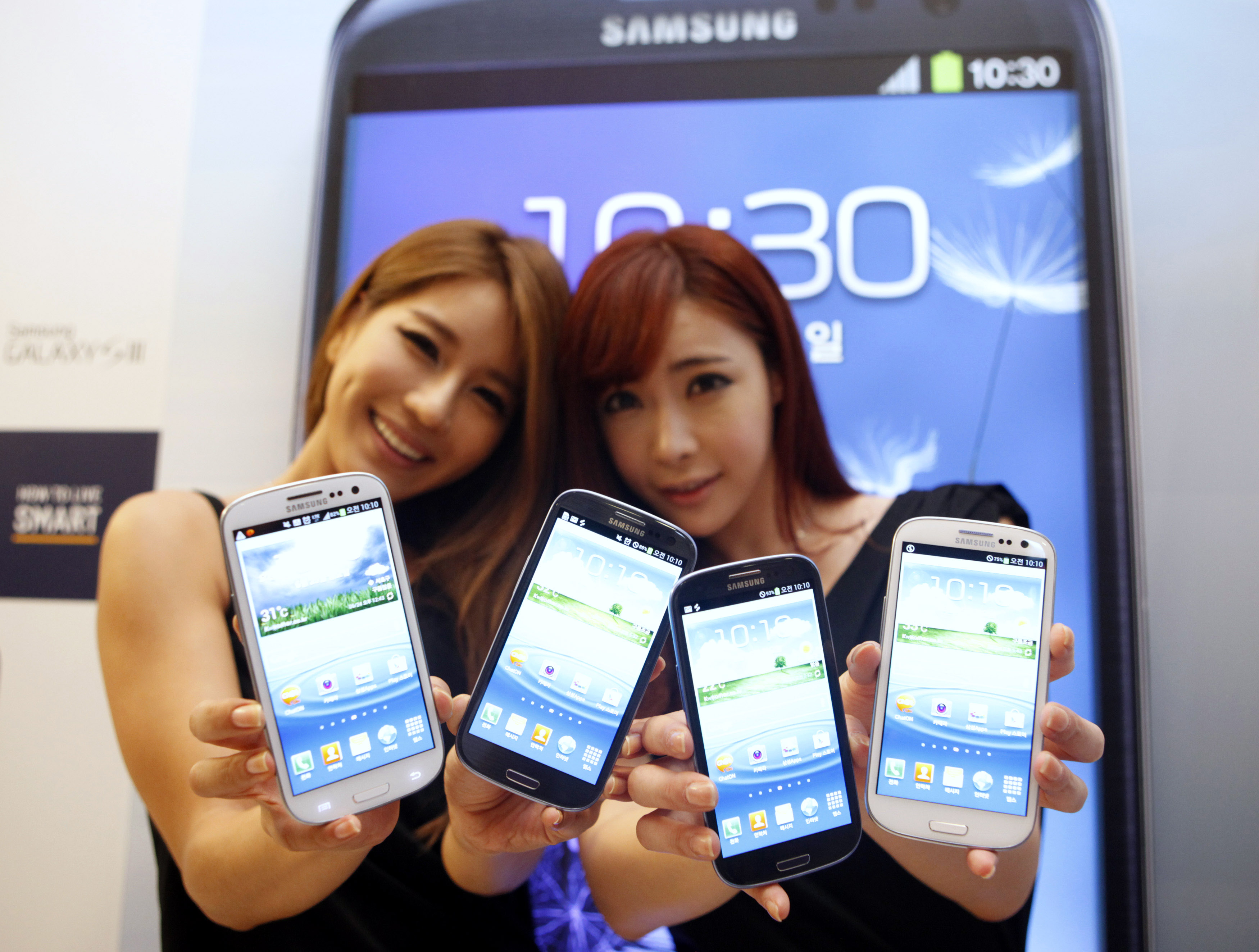 Models hold new Galaxy S III devices as they pose for photographers during an event to launch the smartphone in the local market at the headquarters of Samsung Electronics in Seoul