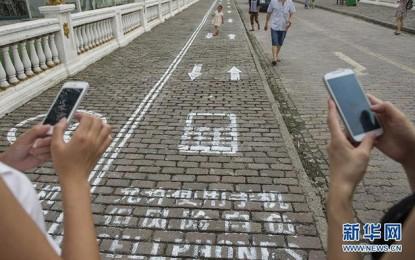 Eljött a vég: Saját sétálósávot kapnak a telefonfüggők Kínában