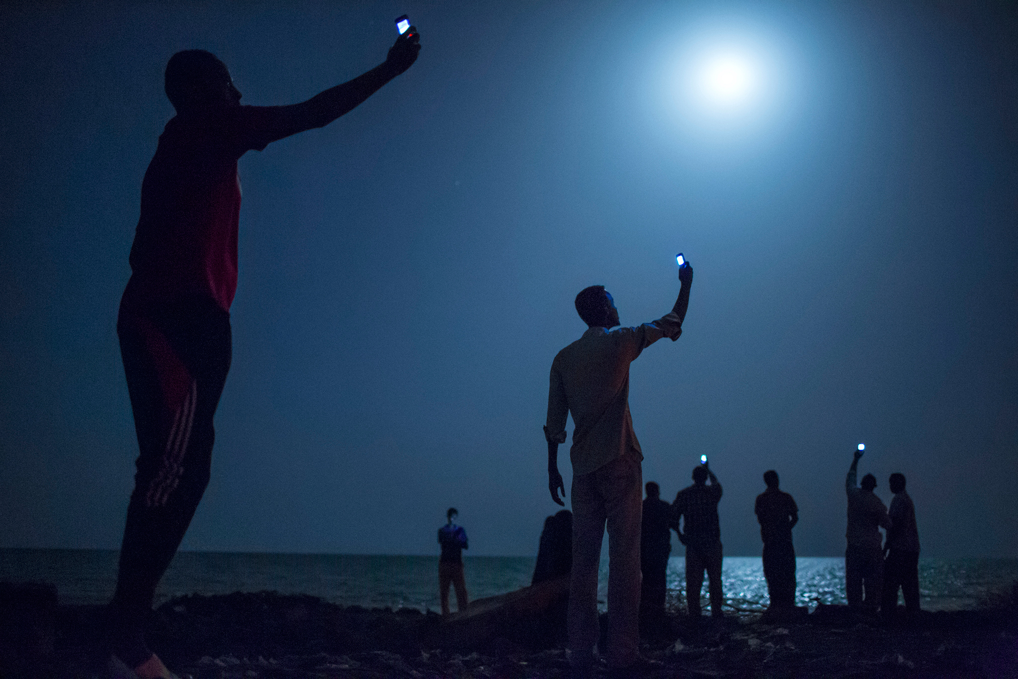 Somali's wave their mobile phones doing what is called among locals as Catching, trying to catch or pickup the mobile phone tower in neighboring Somalia as they stand on Khorley Beach, also called Dead Water Beach, in Djibouti City, Djibouti. As a means to stay in contact with their family and friends back home, one purchases a Somalia SIMM card from the black-market in Djibouti City, placing the SIMM in mobile phone and swinging about the phone in specific areas where a signal might be caught. The best time to catch the signals are at night. Djibouti City to the border of Somalia where the nearest Somali cell tower is located is only roughly 30 miles (48 kilometers) south of the capital of Djibouti.