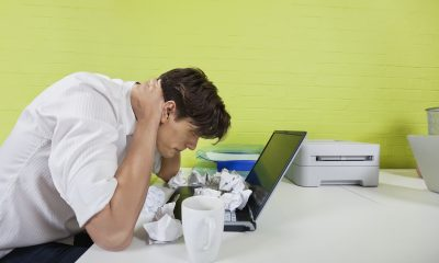 Side view of frustrated young businessman with paper balls and laptop on desk