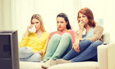home, technology and friendship concept - three sad teenage girl watching tv at home