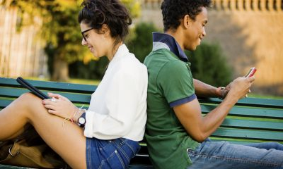 Happy Young Italian Couple using Digital Tablet and Mobile Phone