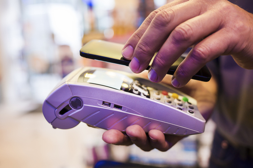 Man paying with NFC technology on mobile phone, in pharmacy