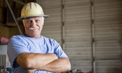 Senior man in warehouse wearing hard hat