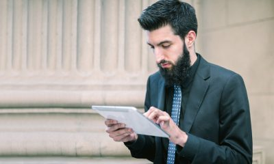 Portrait of a young hip businessman in a suit with briefcase in the financial district using tablet computer