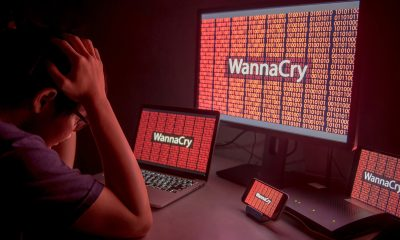 Young Asian male frustrated, confused and headache by WannaCry ransomware attack on desktop screen, notebook and smartphone, cyber attack internet security concept