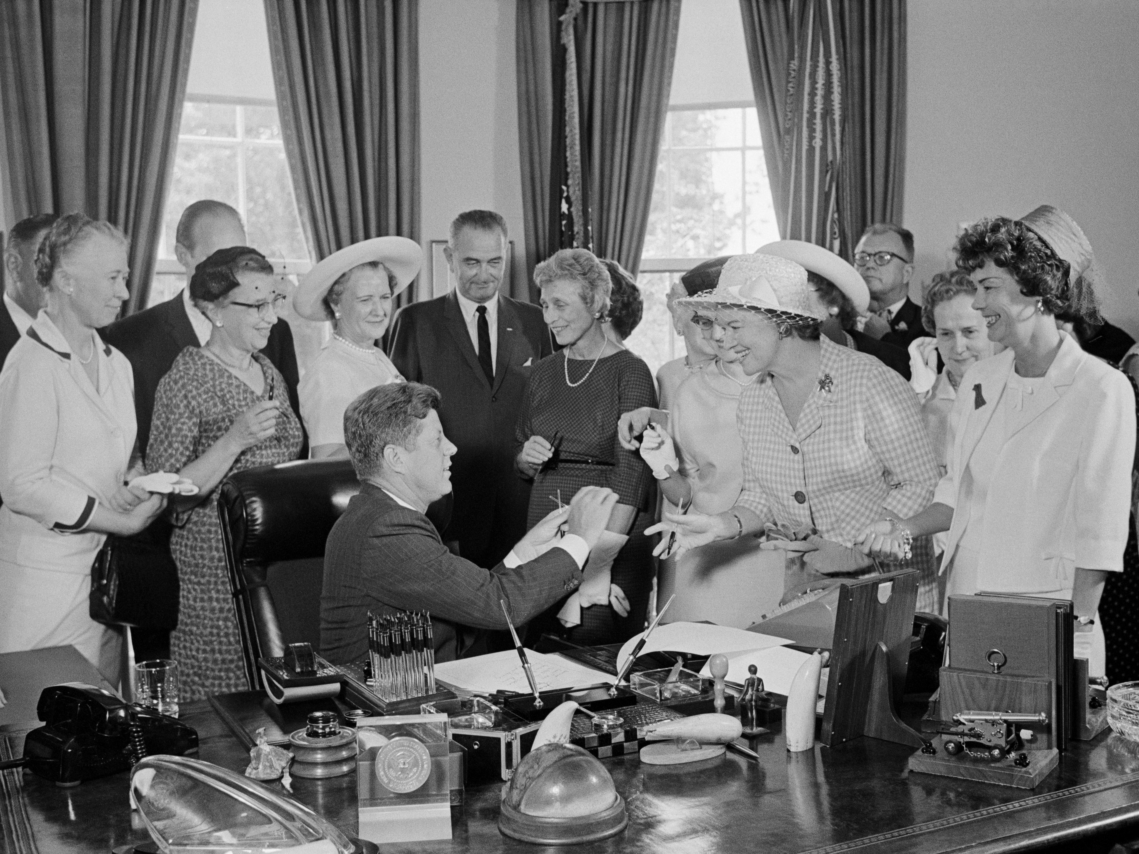 10 Jun 1963, Washington, DC, USA --- Original caption: President Kennedy hands out pens during a ceremony at the White House today in which he signed into law a bill aimed at assuring women of paychecks equal to those of men doing the same work. Left to right: Esther Peterson, Assistant Secretary of Labor; Evelyn Christensen, National Board of YWCA; Rep. Leonor Sullivan (D-Missouri); Vice President Lyndon Johnson; Mrs. Joseph Willen, National Council of Jewish Women; Dr. Minnie Miles, National Federation of Business and Professional Women's Clubs (partially hidden); Miss Margaret Mealey, National Council of Catholic Women; Andrew Biemiller, AFL-CIO Official; Rep. Edith Green (D-Oregon); and Mrs. Garlyn Davis. --- Image by © Bettmann/CORBIS