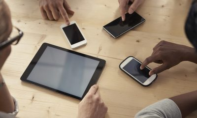 Cropped shot of a group of businesspeople using their digital devices while seated around a table
