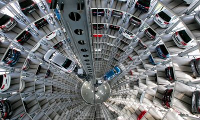 A Passat TSI plug-in-hybrid automobile, left, and a Volkswagen e-Golf electric automobile, produced by Volkswagen AG (VW), are transported on elevation platforms as new VW automobiles sit in storage bays inside one of the automaker's glass delivery towers at the VW factory in Wolfsburg, Germany, on Friday, April 29, 2016. Porsche Automobil Holding SE, the investment vehicle of the billionaire family that controls VW, stuck to a goal of making acquisitions beyond the beleaguered carmaker, even as its dwindling cash on hand reduces the scope of possible transactions. Photographer: Krisztian Bocsi/Bloomberg via Getty Images