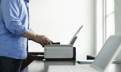 Side view midsection of a mature man using printer at study table in house