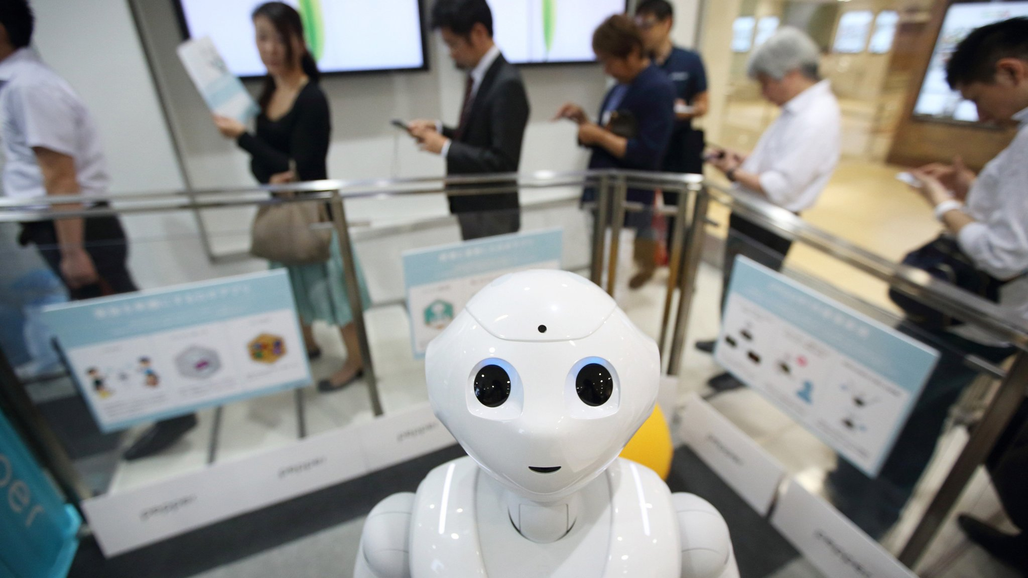 Customers stand in line behind SoftBank Corp.'s humanoid robot Pepper as they wait to pre-order the robot inside the company's store in Tokyo, Japan, on Friday, June 19, 2015. SoftBank will start sales of its Pepper robot to consumers Saturday in a bid to spur adoption. Photographer: Tomohiro Ohsumi/Bloomberg