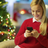 beautiful-blonde-woman-sits-on-a-couch-and-uses-smartphone-christmas-tree-and-room-decorated-with-lights-are-in-the-background-shot-on-red-cinema-camera-4k-uhd_r2m1qg1g9e_thumbnail-full01