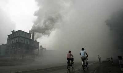(FILES) This picture taken 18 July 2006 shows cyclists passing through thick pollution from a factory in Yutian, 100km east of Beijing in China's northwest Hebei province. China has no plans to radically change its reliance on coal and other dirty fuels despite already feeling the impacts of global warming, a leading Chinese meteorologist said 06 February 2007. In the first official Chinese response to a stark UN report issued last week on climate change, Qin Dahe said China lacked the technology and financial resources for a wholesale conversion to cleaner energy sources. AFP PHOTO/Peter PARKS/FILES (Photo credit should read PETER PARKS/AFP/Getty Images)