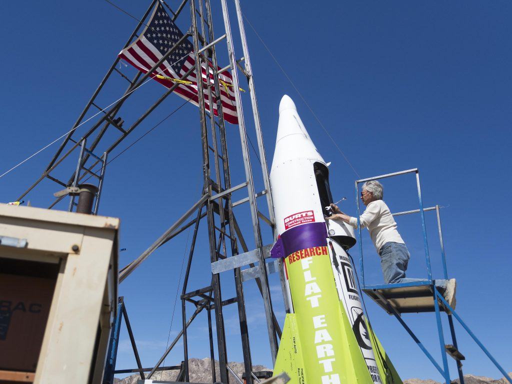 "FILE - In this March 6, 2018, file photo, ""Mad"" Mike Hughes begins work on repairing a steam leak after he scrubbed his launch attempt of his steam-powered rocket near Amboy, Calif. The self-taught rocket scientist who believes the Earth is flat propelled himself about 1,000 feet into the air before a hard-landing in the Mojave Desert that left him injured Saturday, March 24, 2018. Hughes tells The Associated Press that he injured his back but is otherwise fine after Saturday's launch near Amboy, Calif. (James Quigg/Daily Press via AP, File)"