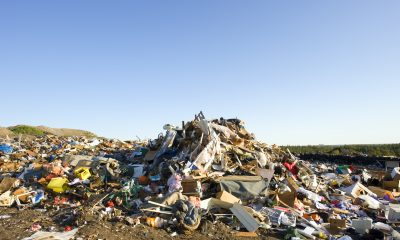 A huge pile of garbage is in the middle of this photograph, spreading out in all directions.  Green grass can be seen behind the garbage on the right side of the image.  The sky above the landfill is a bluish-white near the horizon, fading to a darker blue near the top of the image.  Good copy space at top.
