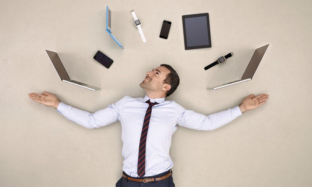 Businessman juggling mobile devices