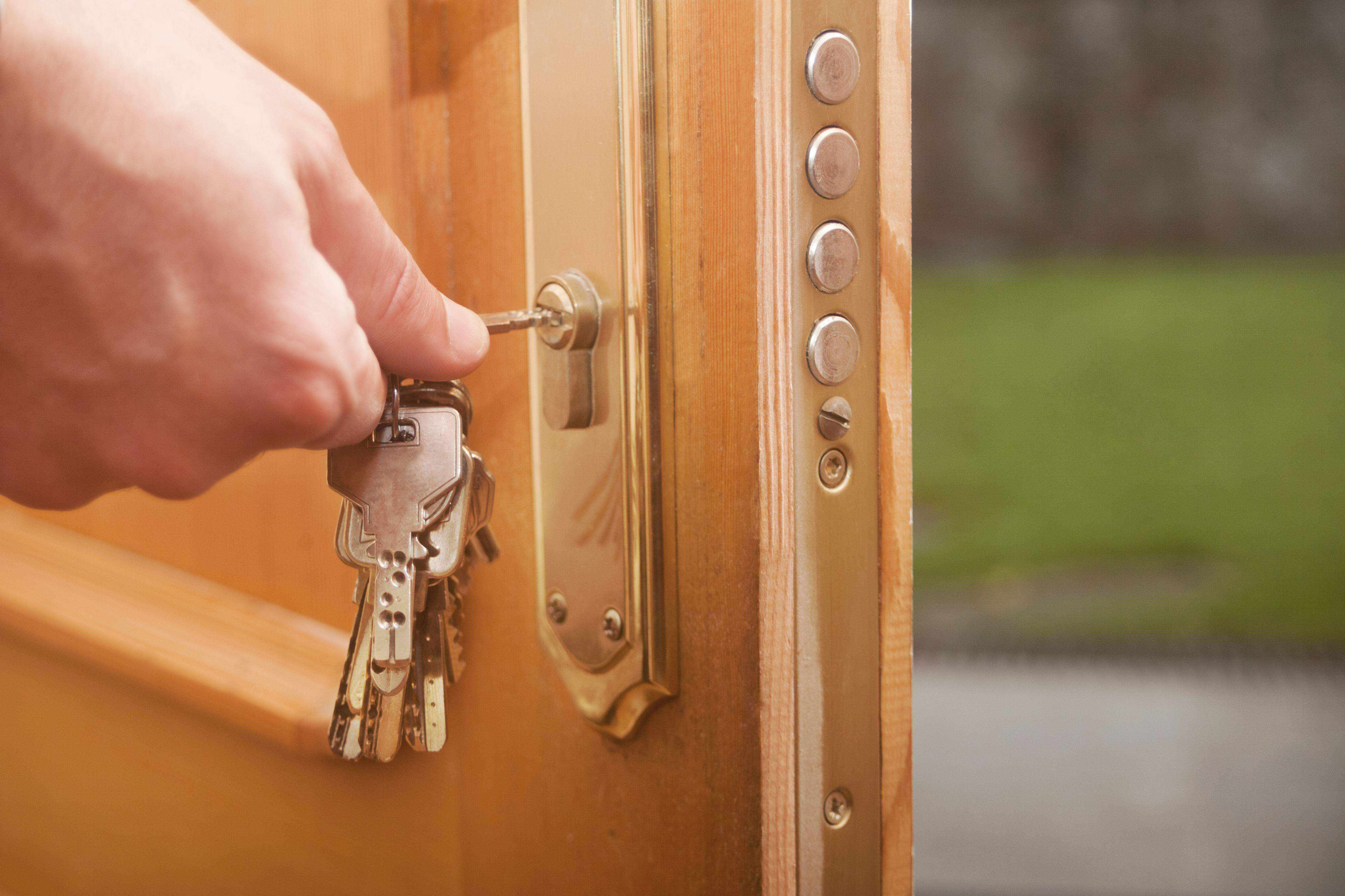 Keys in the open door, male hand placing keys in lock, closing it, garden with green grass outside.