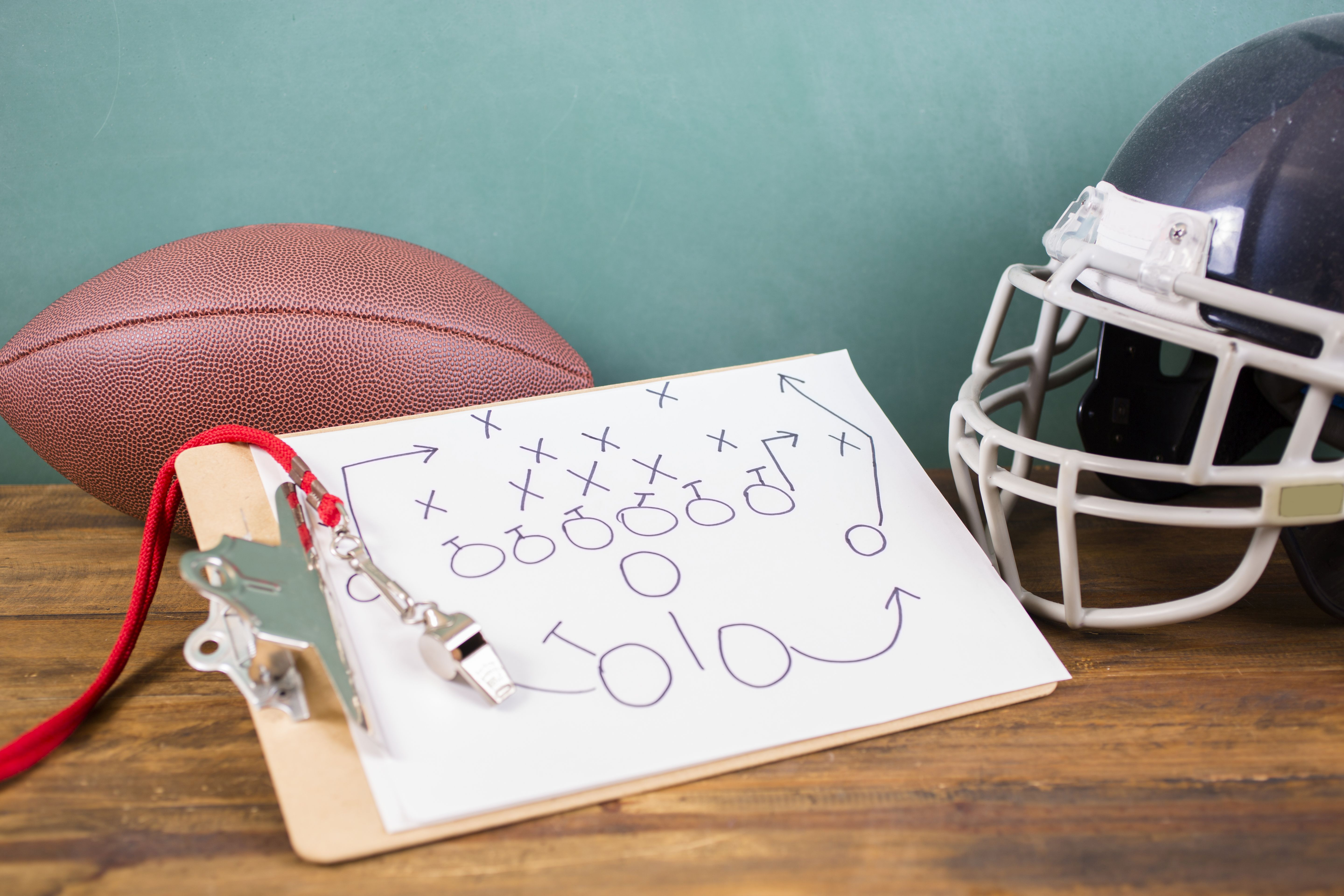 An American football and helmet on a wooden desk with football play diagram drawn on clipboard.  A school coach's silver whistle lies on top.  No people.  Education, sports, teamwork themes.