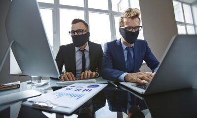 Two businessmen with their mouths tied up typing in office