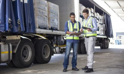 Workers loading and inspecting  a lorry at a large warehouse